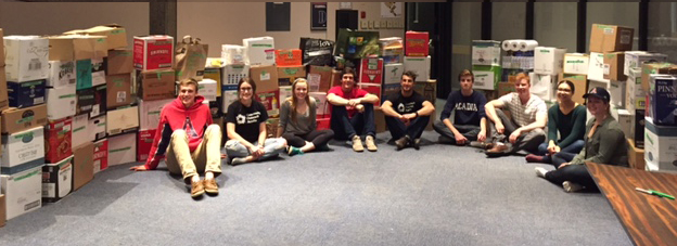 Acadia students with boxes of food from 2016 Trick or Eat Food Drive.